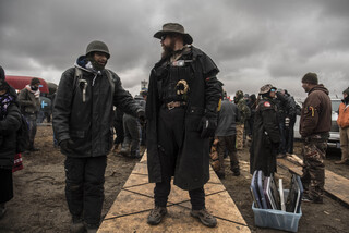 Thelonius stands watch as water protectors build a bridge comprised of planks and foam boards Thanksgiving Day. They built the bridge to travel across part of the river to Turtle Island, a sacred burial ground recently overtaken by police.